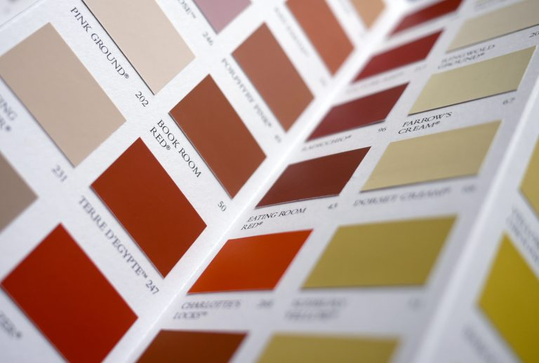A paint swatch book showing hues of reds, yellows and neutrals