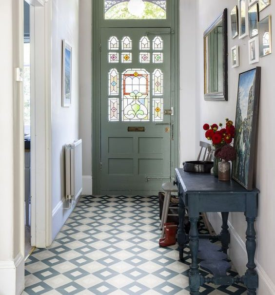 A beautiful Victorian style entrance hall with lovely patterned tiles, and an original stained glass front door.