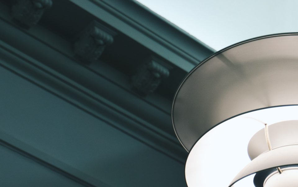 An decorative piece of coving painted in a dark green next to a modern lampshade