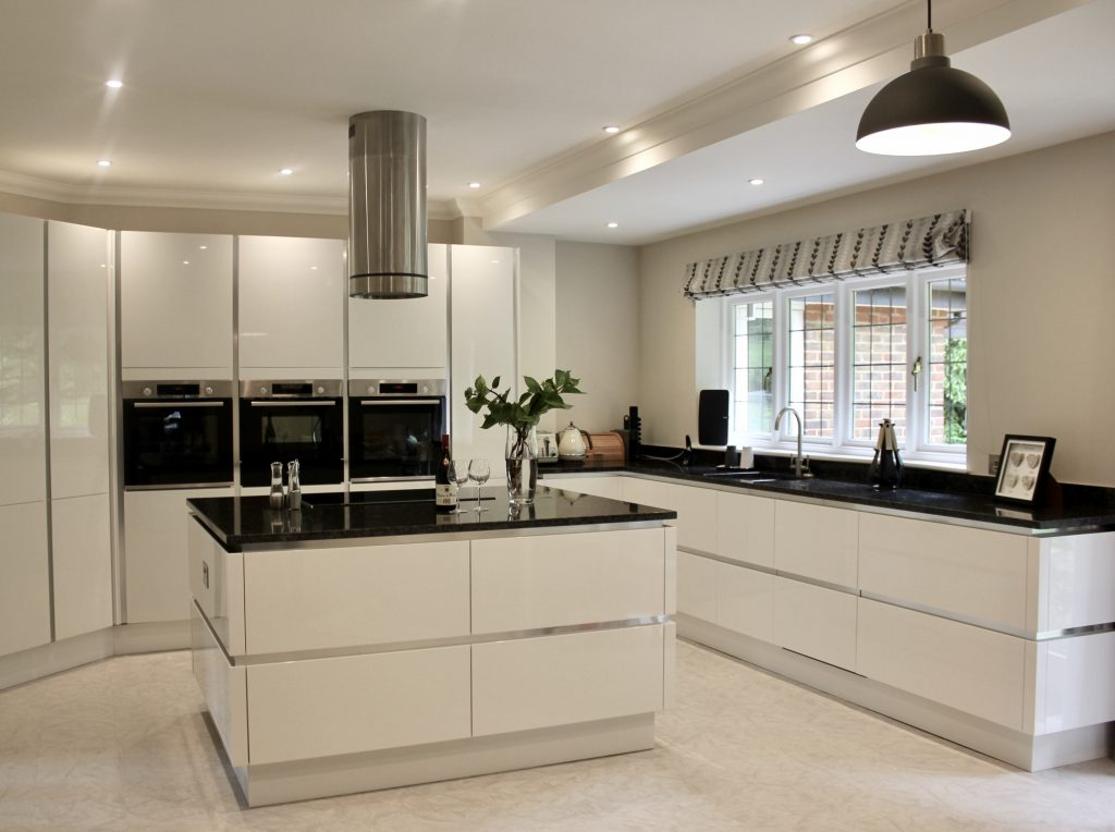 Interior Design – A modern clean white kitchen with an island and black worktops